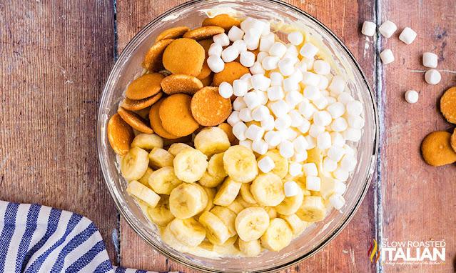 banana pudding cheesecake mixing in cookies, bananas and marshmallows