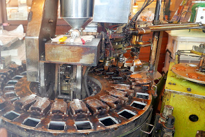 In this ningyo yaki machine, it automatically does the entire process in an automated fashion. The crane carries the cooked cake to the machine on this right side to cool and get packaged down the little slide of plastic you see. On the left you can see the brushing inside the mold and then the squeezing of dough to the left of that