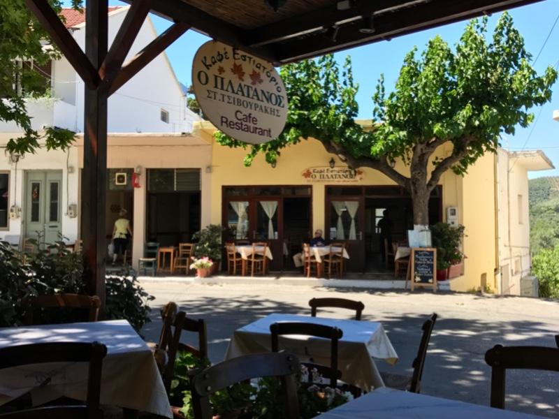 Utsikt fra en overbygget terrasse med bord og stoler. På den andre siden av en vei er en gul restaurantbygning med bord på utsiden.