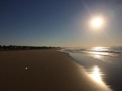 En lav morgensol over en øde strand