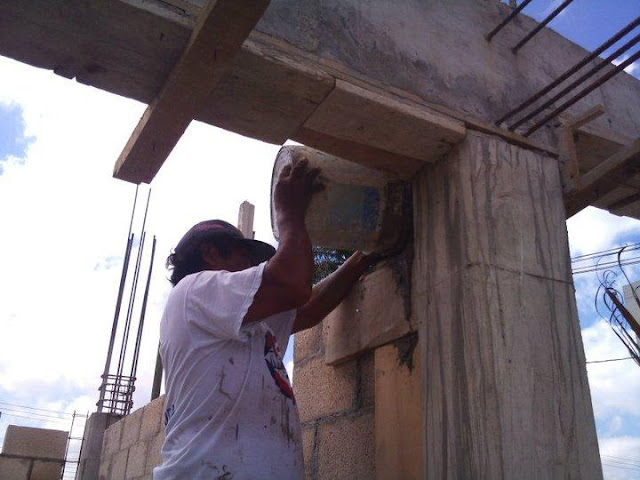 Isaias, the master mason, pouring the supports.