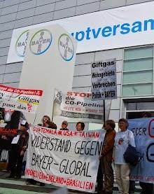 Demonstranten vor der Hauptversammlung mit Transparenten: »Guatemala, USA, Taiwan, Indonesien, England, Brasilien. Widerstand gegen Bayer – global.«, »Stop CO-Pipeline«, »Giftgas durch Wohngebiete ist ein Verbrechen von Profit + Bayer«.