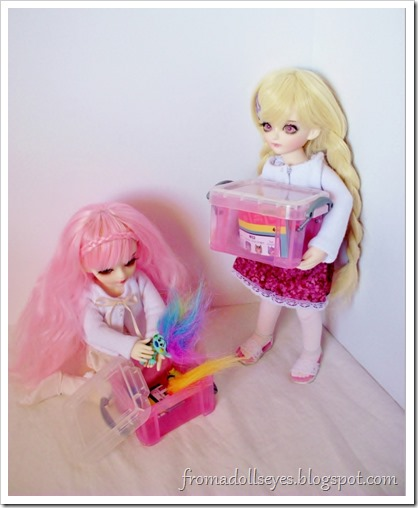 Two ball jointed dolls putting away their toys.