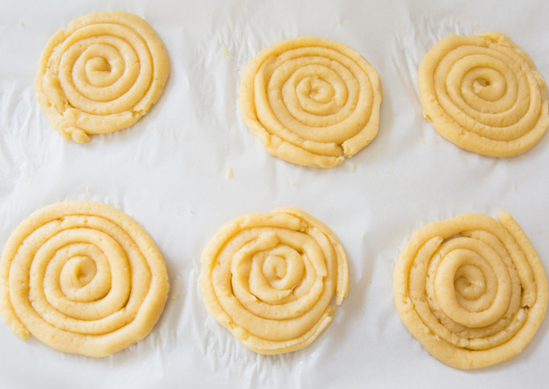 overhead photo of churro dough piped into spirals on a baking sheet
