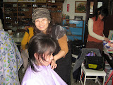 Bi-ling cutting hair at the Home of God's Love