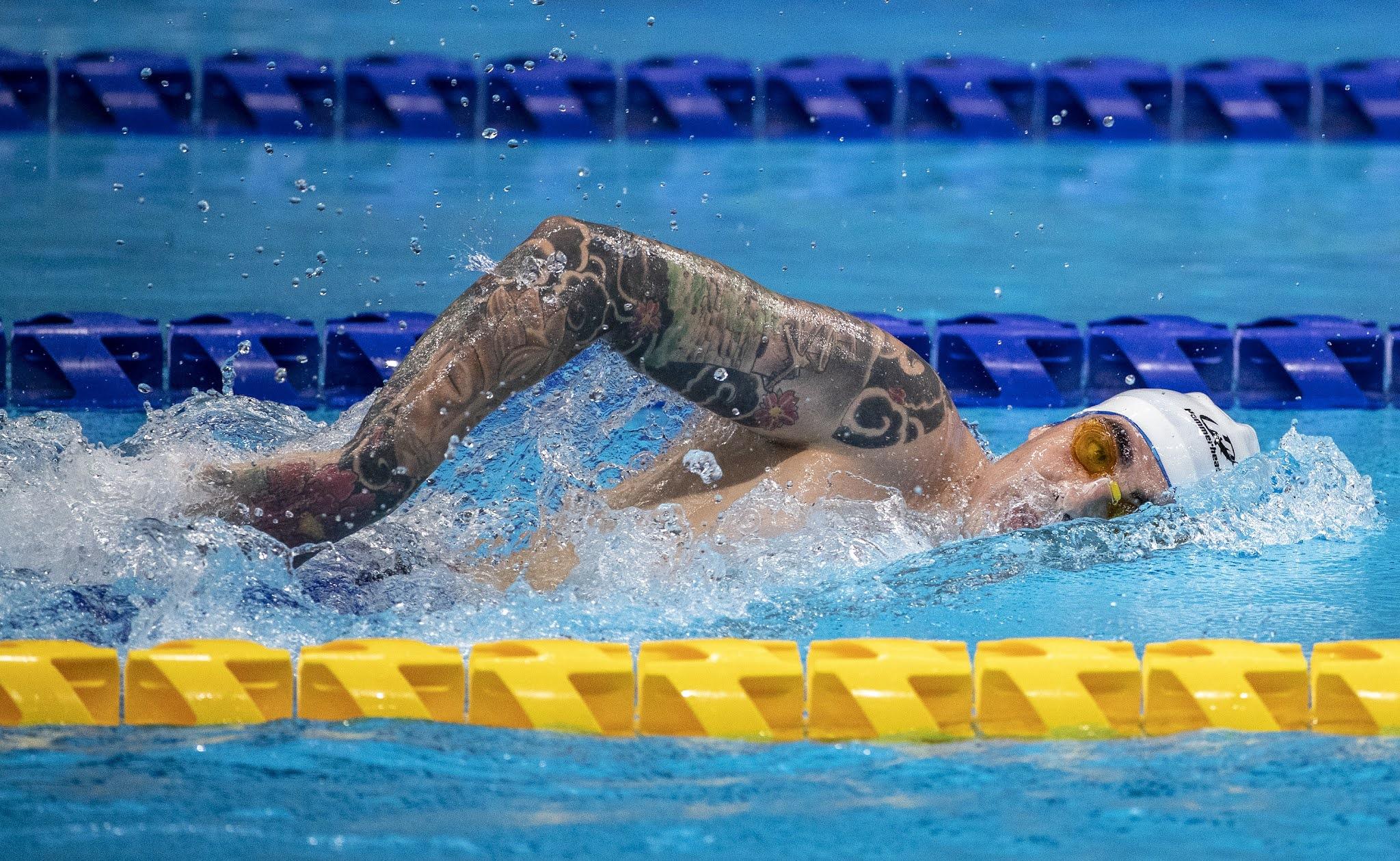 Talisson Glock fazendo o nado livre. Ele usa uma touca branca e óculos laranja. Talisson está com metade do rosto e um braço coberto de tatuagens para fora da água.