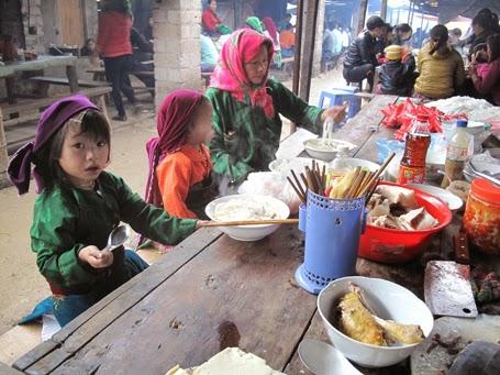 Đi chợ mua đồ đã xong, lũ trẻ nhỏ được mẹ cho ăn phở nóng – món ăn của người miền xuôi đem đến bán.