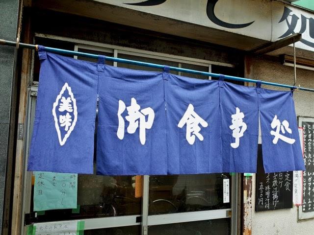店頭に掛けられた青いノレン。「お食事処」と書かれてる