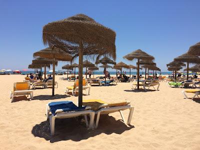Solsenger og parasoller på stranden.