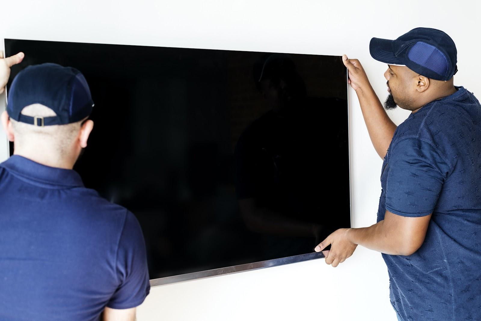 Dois técnicos instalando uma televisão.