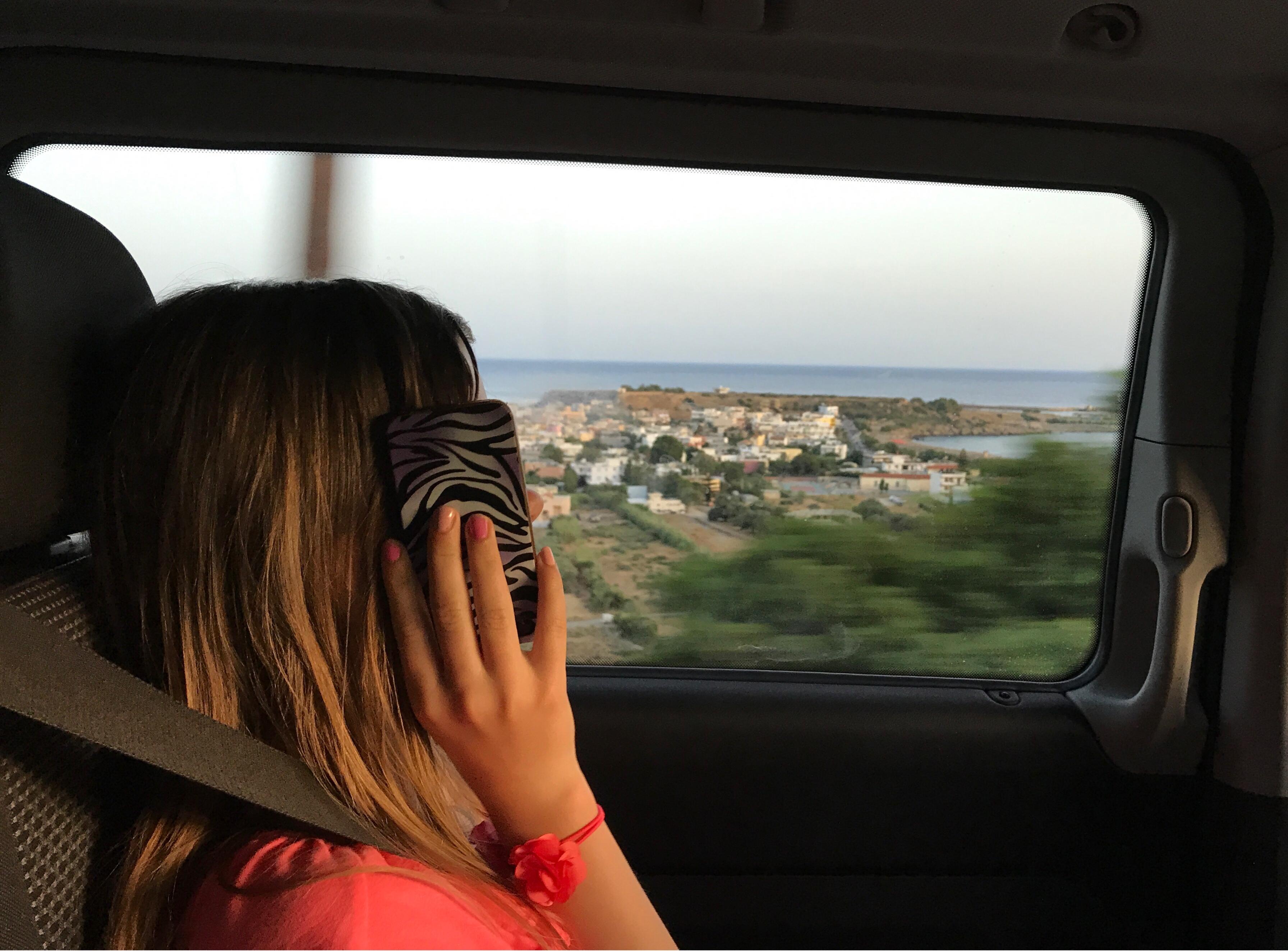 Gjennom sideruta på bilen ser man en by på en halvøy med havet på begge sider. Jente med telefon i forgrunnen.