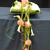 D'un coixí floral de clavell blanc penja una estructura de la qual se subjecten unes grosses roses i cauen unes cales blanques.
