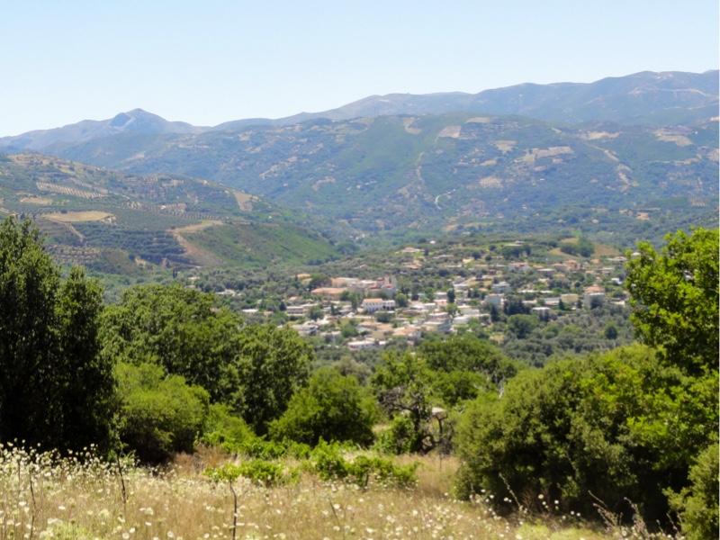 Hvit landsby sett på avstand. En blomstereng og trær i forgrunnen. Grønne fjellsider i bakgrunnen.
