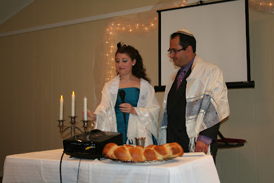 Vivienne reciting the prayer over the Shabbat candles and then lighting them.