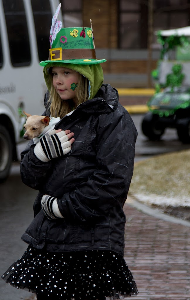 A spectator keeps her dog warm during the worst of the storm.