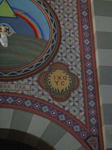 """Em latim: """"iri nomine jesu"""" que quer dizer """"o nome de jesus"""". A coroa de oliveira simboliza a paz que o homem alcança na sua reconciliação com Deus e com o próximo. Encontramos também as letras I X O Y C, abreviação de I H C O Y C, nome de Jesus Cristo em grego."""