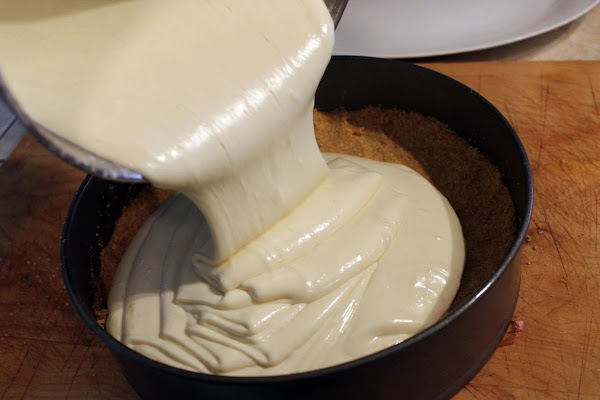Cheesecake batter being poured into a pan.