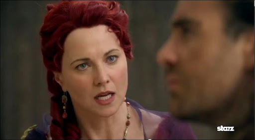 Lucretia (Lucy Lawless) bids Gannicus (Dustin Clare) to rid Capua of Gaius Claudius (?) Glaber. Notice the red wig she wears when she wishes to channel her dead friend, 'Gaia?' Gaia was murdered in 'Spartacus: Gods of the Arena,' a prequel which prominently featured Clare.