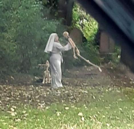 Woman dressed as nun seen dancing with skeletons in graveyard
