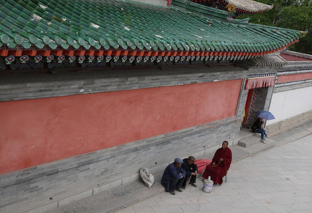 Tibetan monk and two other men sitting at Kumbum Monastery (Taer Si) in Qinghai, China