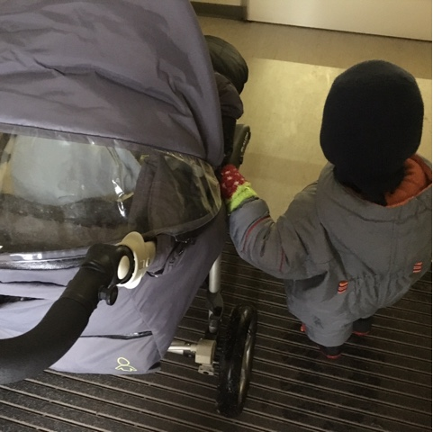 Kind am Kinderwagen