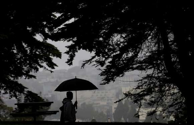 A man and woman walk along a path under trees at Alamo Square Park in San Francisco, 3 March 2016. Light rain has started in the San Francisco Bay Area as the region braces for a series of storms expected this weekend and into next week. Photo: Jeff Chiu / AP Photo