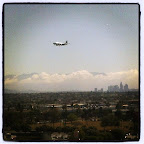 View of DTLA, mountains, clouds, and an airplane.