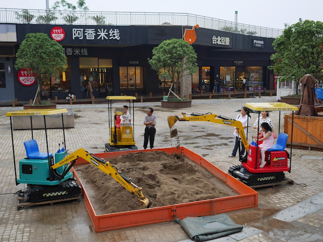 kids in a toy diggers at a sandbox outside of the BBG shopping mall (步步高生活广场) underneath Dongfanghong Plaza in Xiangtan, Hunan