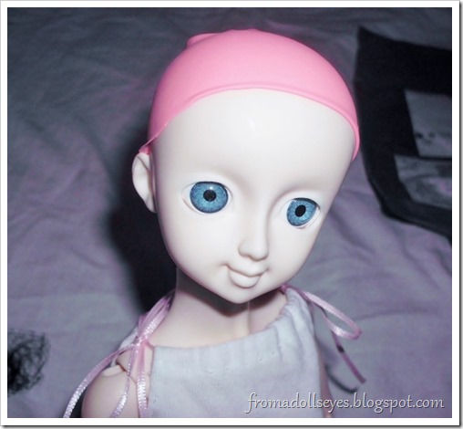 Ball jointed doll wearing a balloon wig cap.