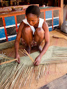 "A lady weaving together a ""tsihy"" (a grass mat) at the town before walking to Antenina."