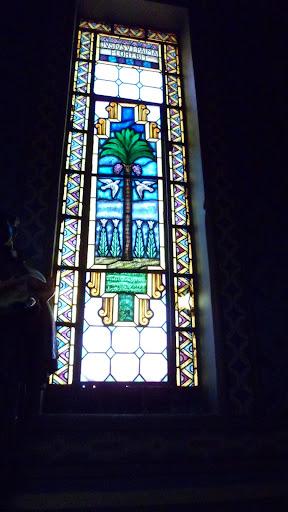 """Tem-se, no vitral direito, a figura da palmeira. A frase em latim, na parte superior do vitral, complementa a informação do vitral esquerdo: """"O justo se multiplicará como cédulas do Líbano""""."""