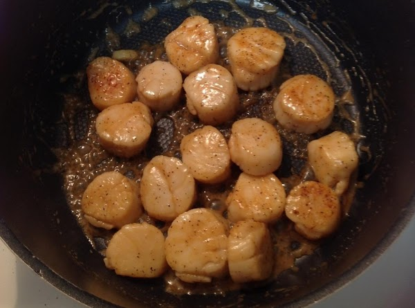 Sprinkle scallops with salt and pepper. In a large skillet, saute scallops in 1...