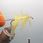 2. Wykonuję tułów z kremowo zółtej wełny, na przedniej części tułowia nawijam pierwszą jeżynkę z koguciego piórka, wszystko wzmacniam lametą. Następnie przywiązuję piórko na drugą jeżynkę – pozbawione z jednej strony promieni, barwione na żółto piersiowe pióro kaczora krzyżówki.