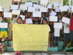 A class of smiling children with thank you messages