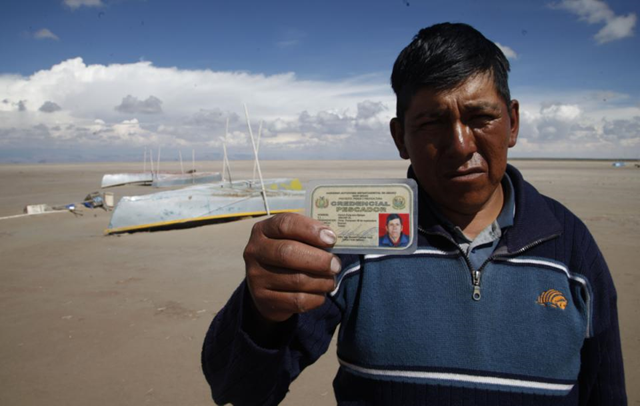 In this 12 January 2016 photo, Abraham Fulguera shows his fisherman's credential, in the dried up Lake Poopo, on the outskirts of Untavi, Bolivia. 'I am the president of the September 10 Fishing Cooperative. We used to be 30 fishermen and there used to be ten or more fishing cooperatives in Lake Poopo. Now we work as construction laborers. Others have left to look for jobs. I hope we do not become a ghost town. We have faith that the lake will come back.' Fulguera said. Photo: Juan Karita / AP Photo