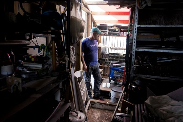 Jesse Vazquez in his home in Bayamon, Puerto Rico, with the generator that his children brought with them from New York. Photo: Jose R. Madera / Yahoo News
