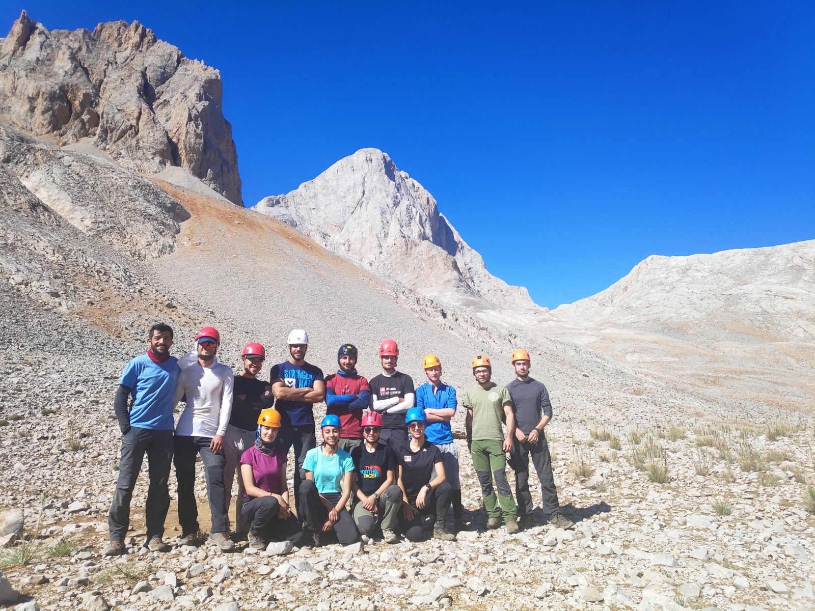 A group of people standing in front of a mountain  Description automatically generated