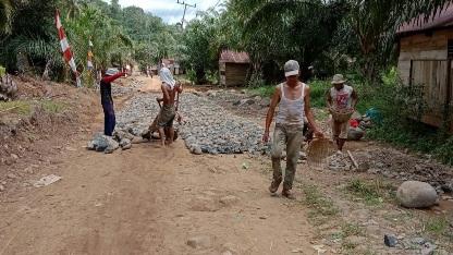 Peluh Keringat  Tak Kendorkan Giat Pemasangan  Batu Kali Pengerasan Jalan  di TMMD Kodim