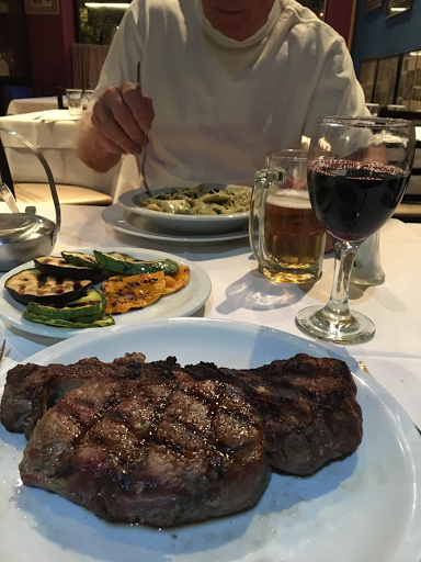dinner table in restaurant with large steak on and plate of pasta