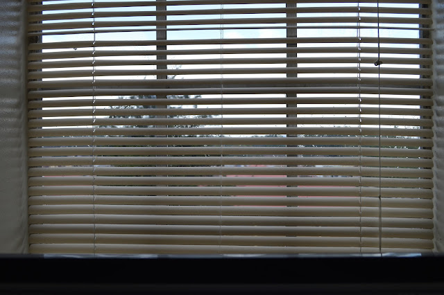Window with blinds partially open, looking out into a gray day