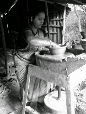 An woman in pottery village busy in making potteries