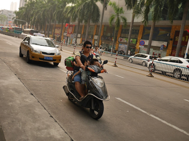 two small children riding a scooter in front of the man who is driving in Zhongshan, Guangdong