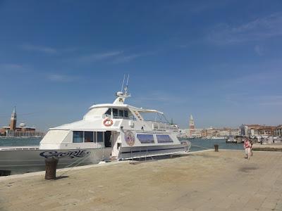 En nokså liten, to-etasjers båt som ligger til kai i Venezia.