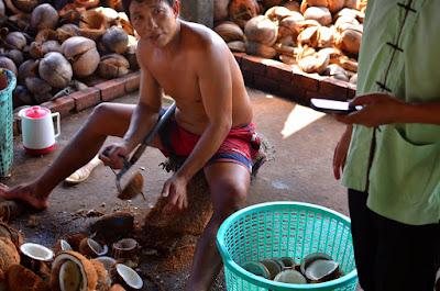 A man shells coconuts
