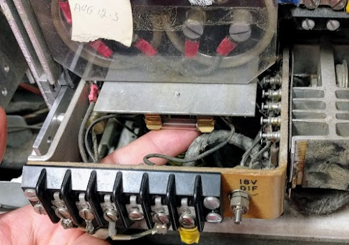 The 18V differential power supply in the IBM 1401 provides 12 volts to the core memory. The fuse is under the large electrolytic filter capacitors.