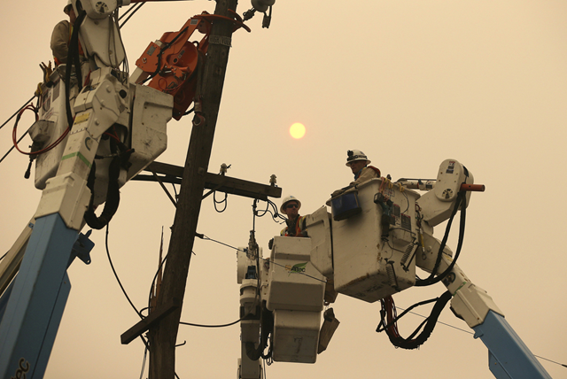 In this 9 November 2018 file photo, Pacific Gas & Electric crews work to restore power lines in Paradise, California. Facing potentially colossal liabilities over deadly California wildfires, PG&E will file for bankruptcy protection. The announcement Monday, 14 January 2019, follows the resignation of the power company's chief executive. Photo: Rich Pedroncelli / AP Photo