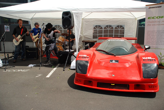 Fast, sleek, red electric racing car with the band playing alongside it.