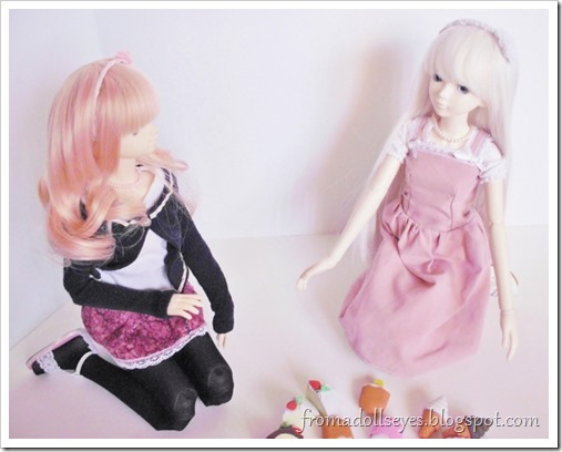 Two ball jointed dolls looking at the assortment of cake shaped food erasers.