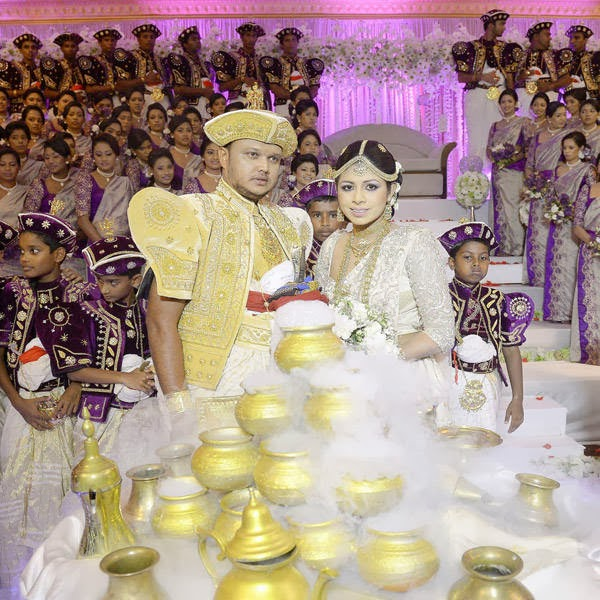 Sri Lankan wedding couple Nisansala (R) and Nalin (L) pose for photographers during their Guinness World Record-breaking wedding in Negombo, some 30kms north of Colombo, on November 8, 2013. Including 126 bridesmaids, 25 best men, 20 page boys and 23 flower girls the wedding breaks the previous record, held by a wedding in Bangkok that included 96 bridesmaids.