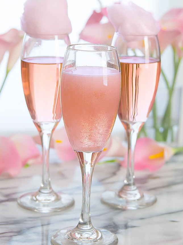 photo of a fizzy glass of champagne with two other glasses in the background